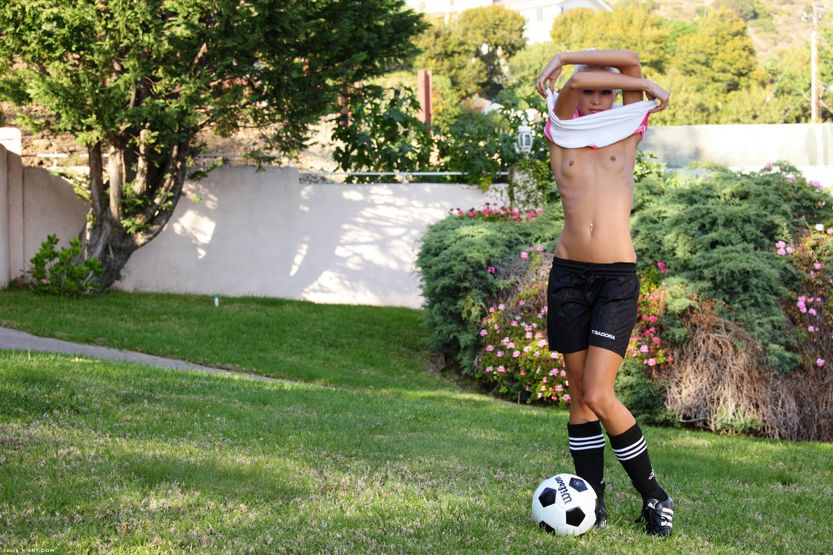 Skinny blonde girl uncovers tiny tits while bouncing a soccer ball outdoors