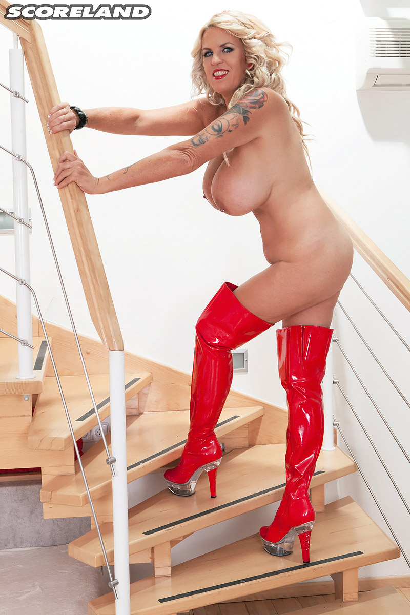 Big titted blond Shannon Blue doffs red latex dress to model in matching boots