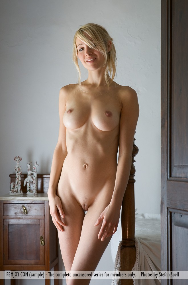 Sexy slut Corinna wraps her naked legs around the bed post with big tits bare