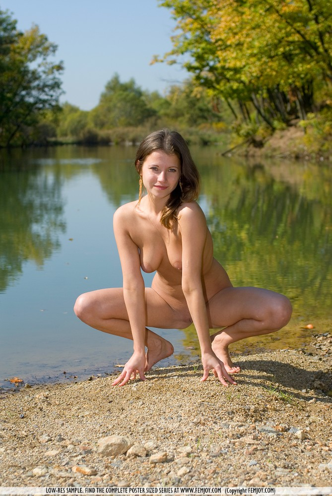 Hot young Angilie splashes stark naked in the river displaying her wet ass