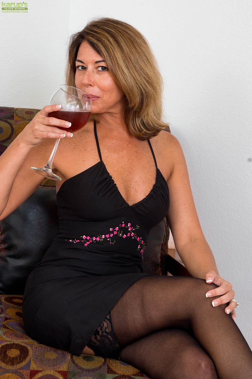 mature housewife niki may takes a sip of wine before showing her