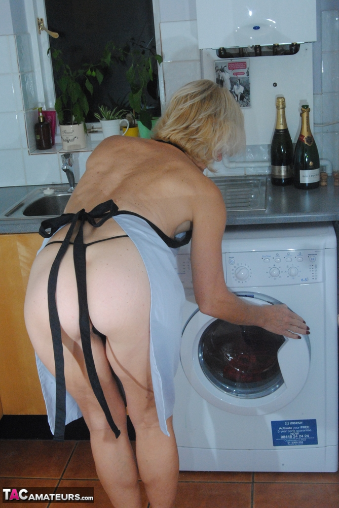 Mature MILF with blonde hair wears only an apron while devouring a banana