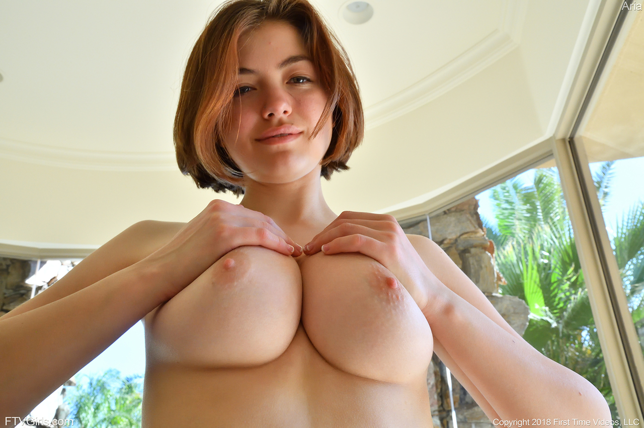 Pretty natural redhead Aria-II undressing outdoors to flaunt her nice big tits