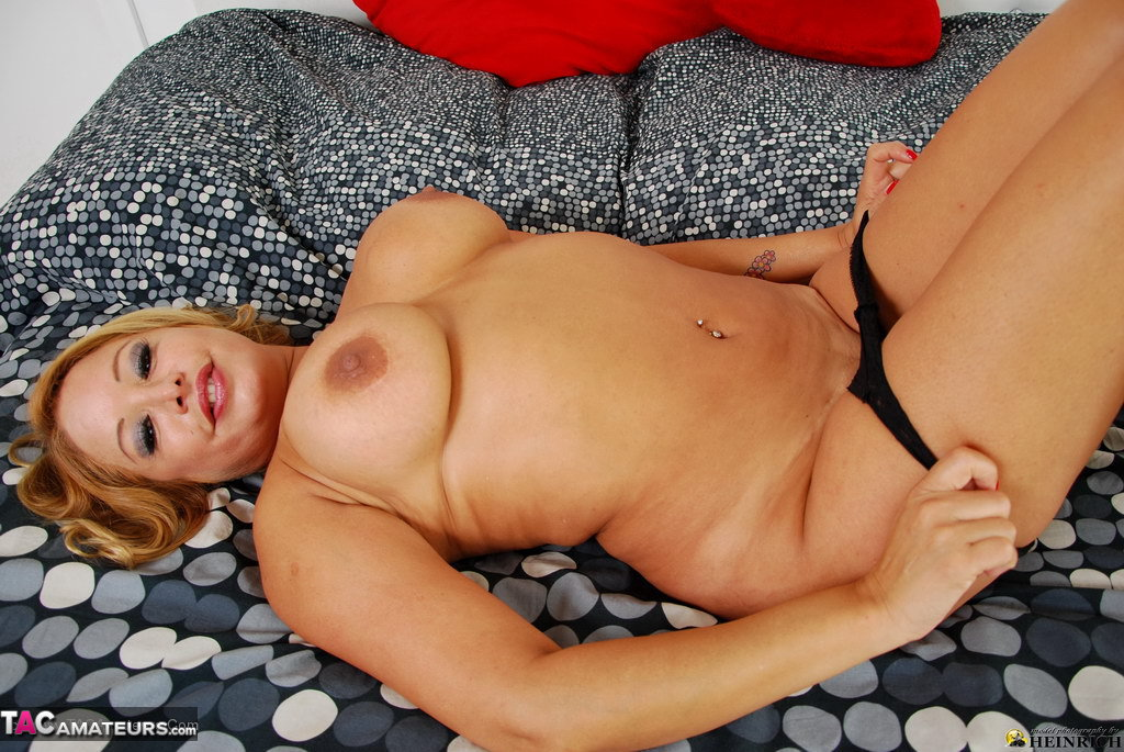 Blonde first timer holds her large boobs as she takes off lingerie
