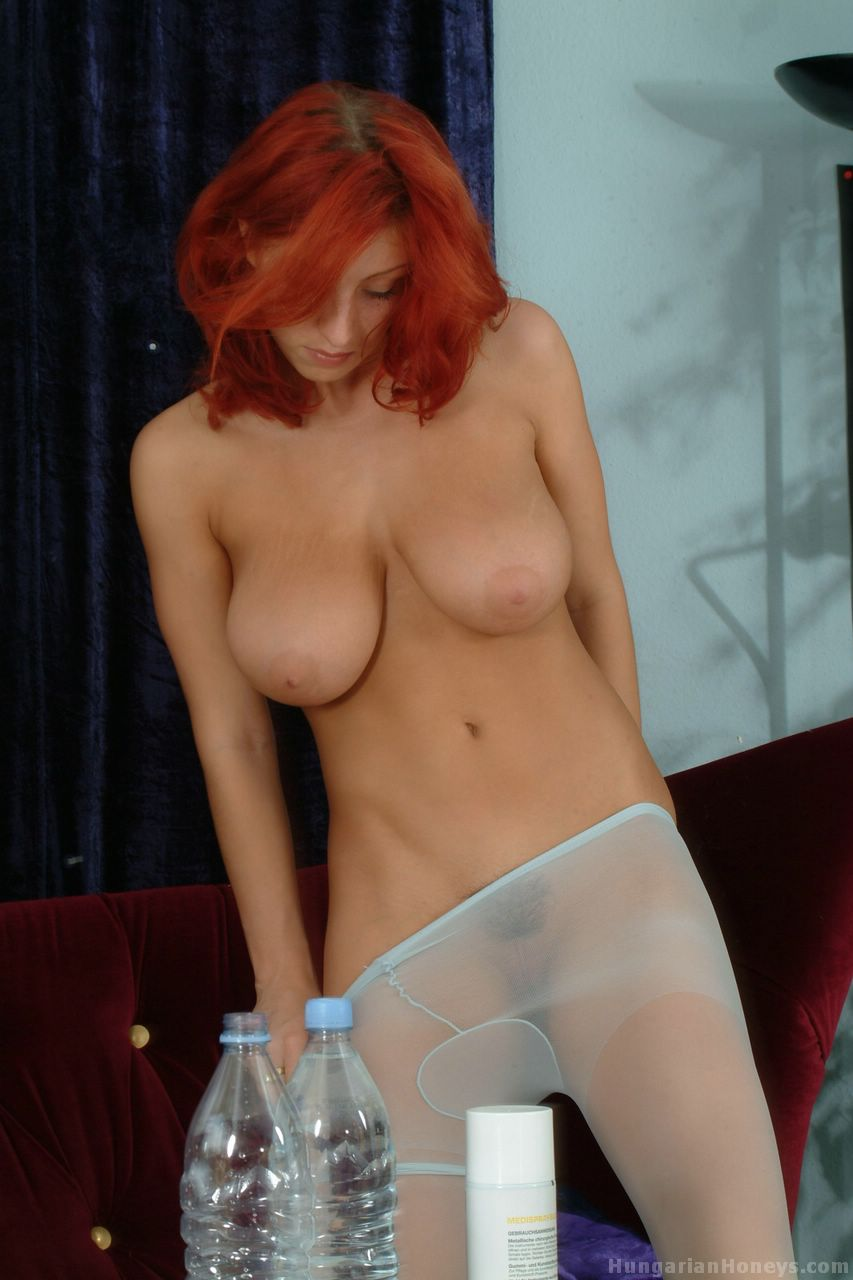 Redhead MILF Ashley Robbins shows off her large breasts in pantyhose