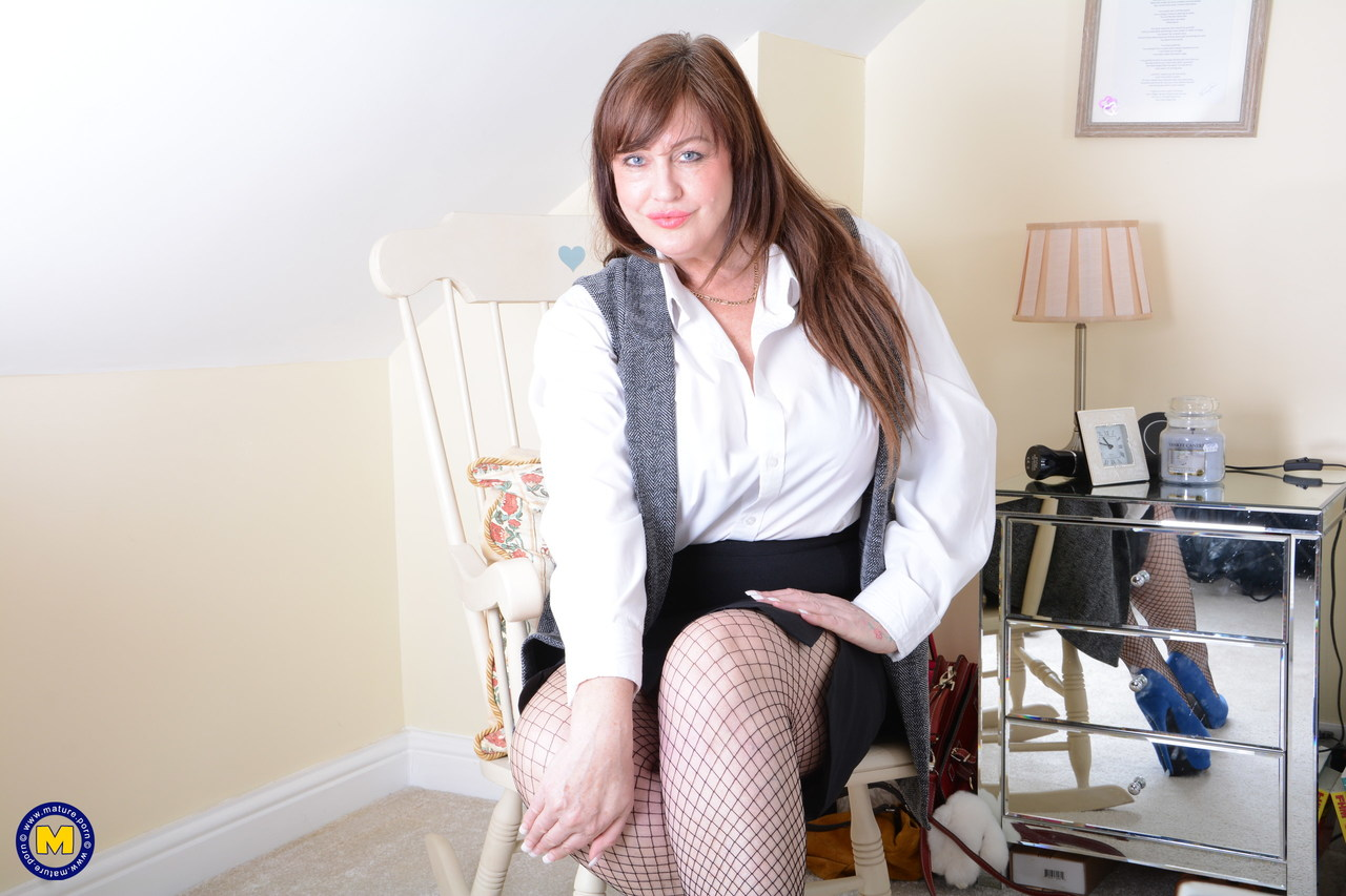 Thick woman removes business attire before masturbating in mesh stockings