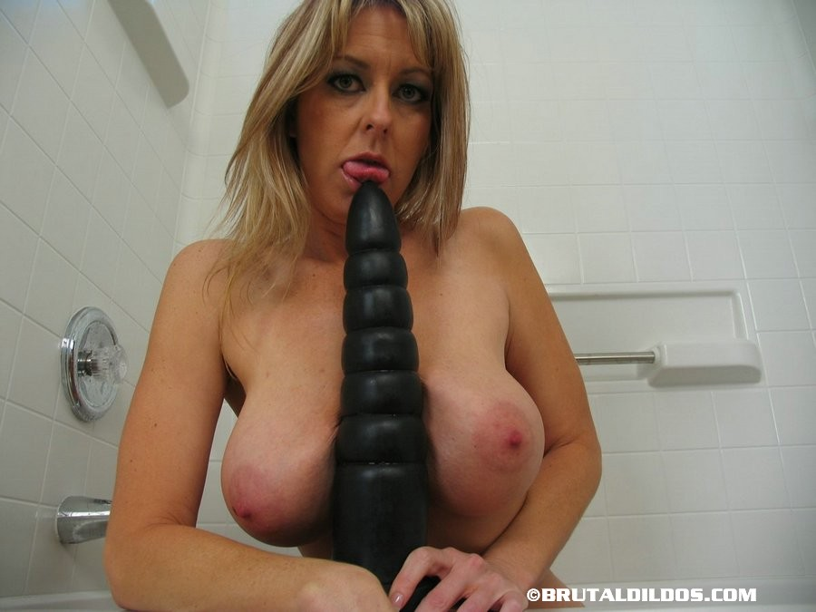 Big titted older woman Heather rides a huge black dildo on side of bathtub