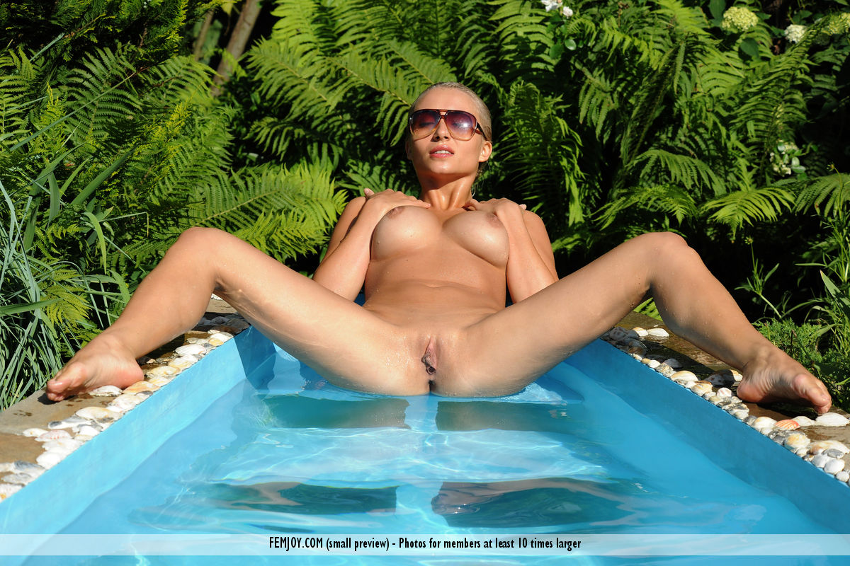 Busty blonde Ella C showcases her pussy while lounging in outdoor pool