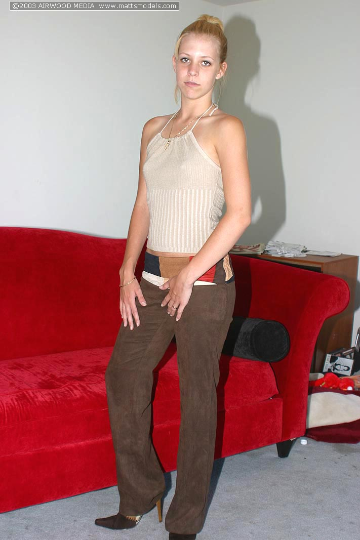 Slender young girl Leah shows the pink of naked pussy on red couch