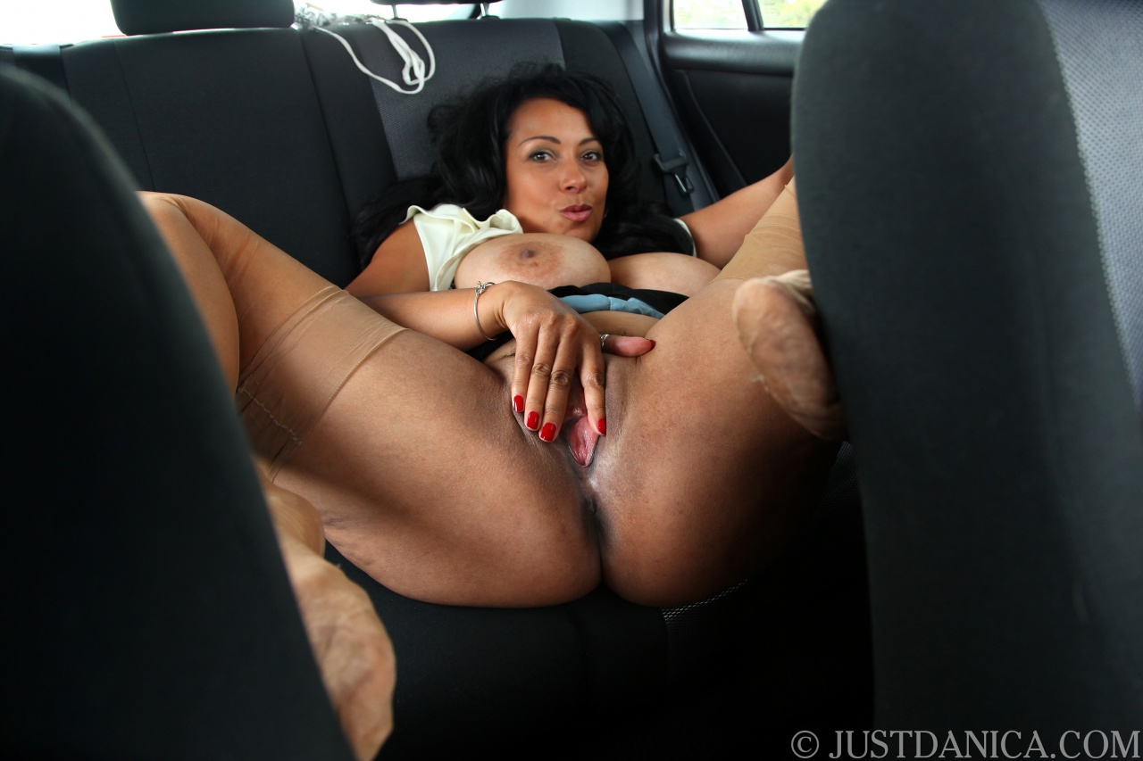 Hot mature lady Danica Collins exposes her big tits and pussy inside a car