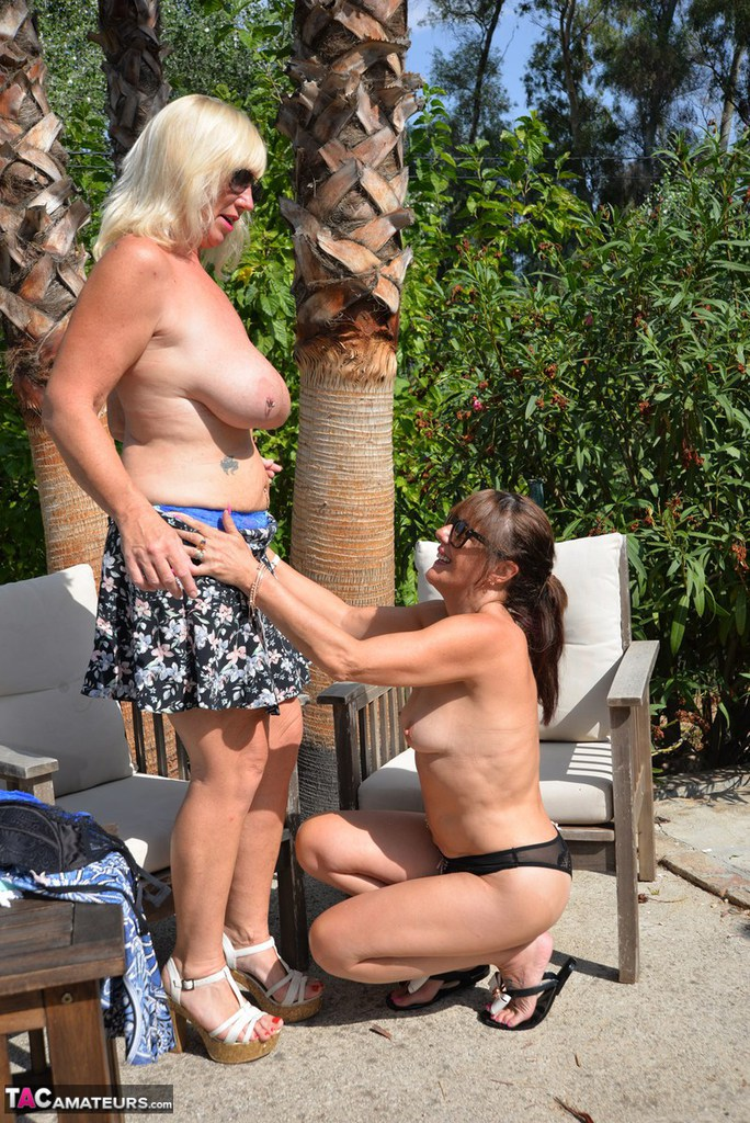 Overweight lesbians in sunglasses help each other get naked on wooded patio