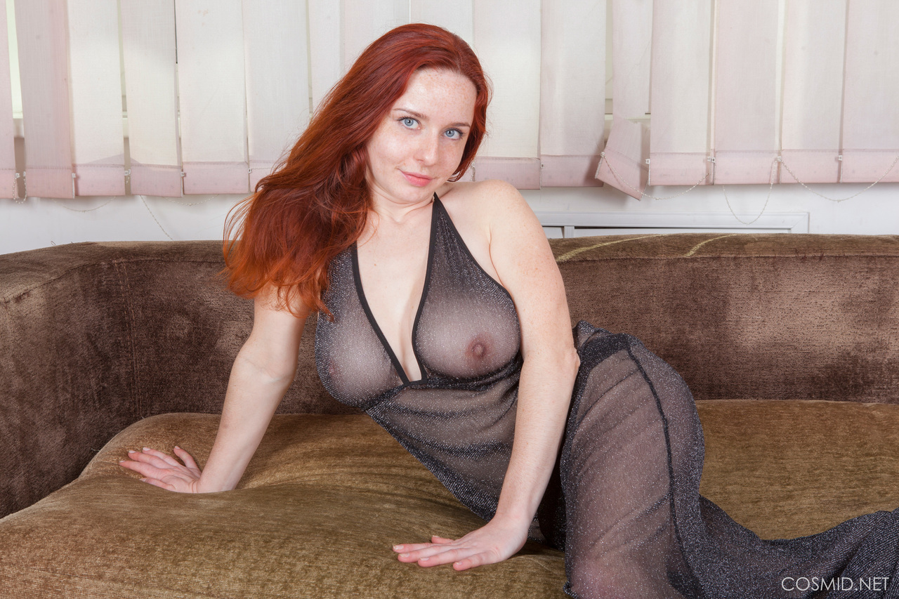 Redhead model Sara Nikol frees her natural tits by removing see thru lingerie