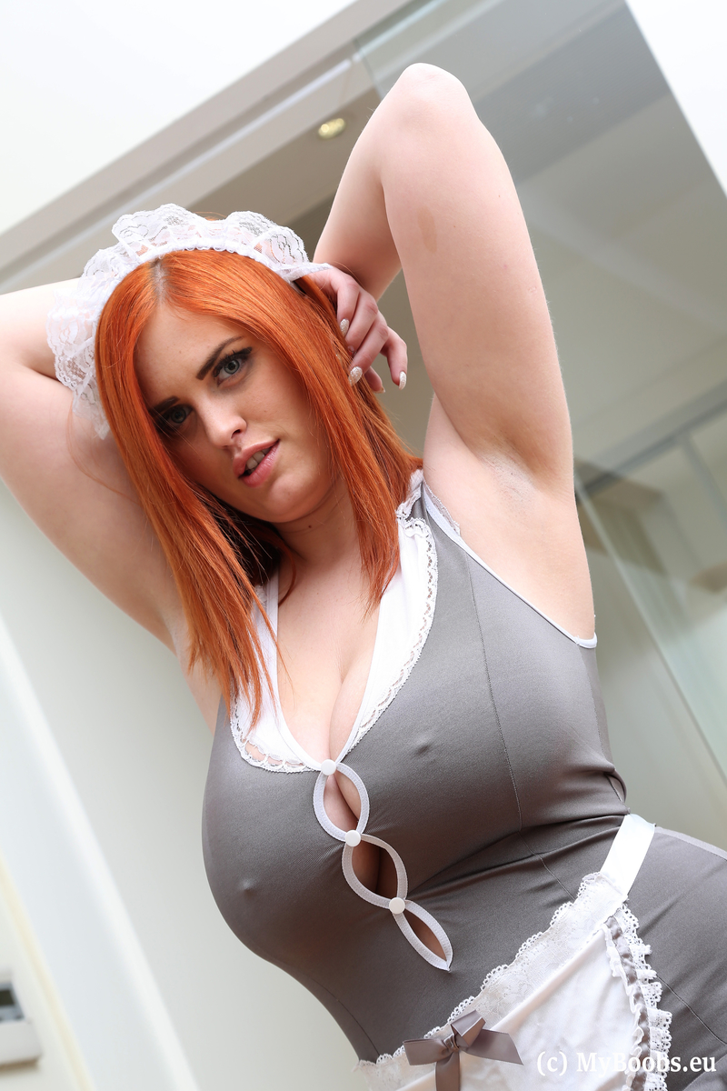 Redhead maid Alexsis Faye licks a nipple after freeing huge tits from uniform