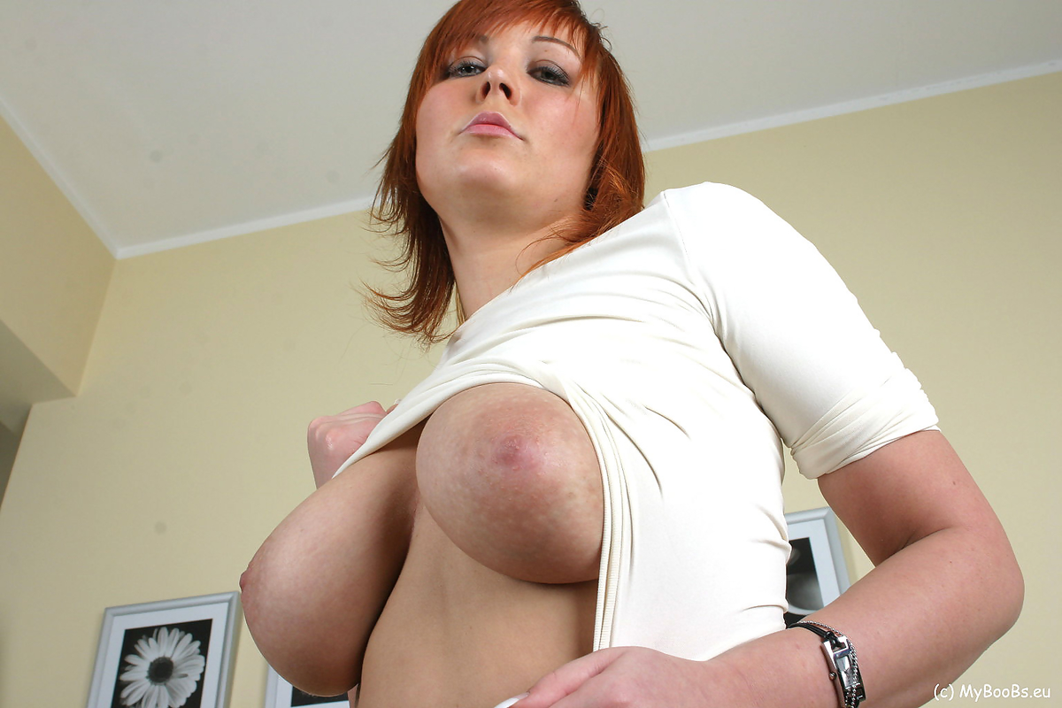 Redheaded model Ania Colette display her large boobs in a black miniskirt