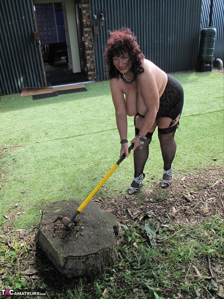 Fat amateur with huge floppers handles an axe on chopping block before a swing
