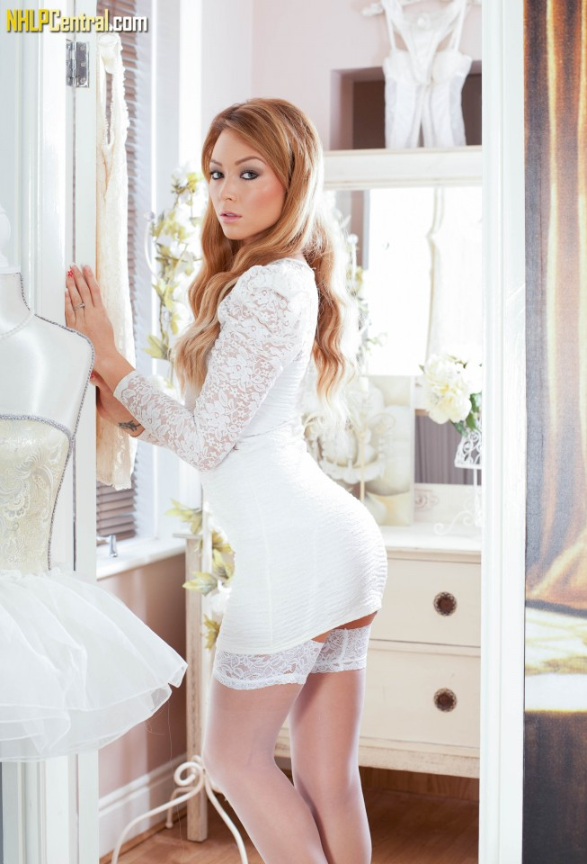 Redhead model Natalia Forrest showcases her shaved pussy in white stockings