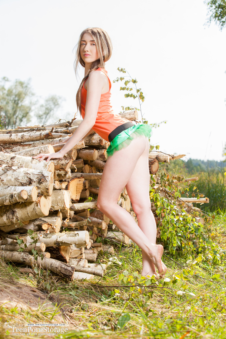 Petite teen with hair to her tight ass Lada poses naked afore firewood
