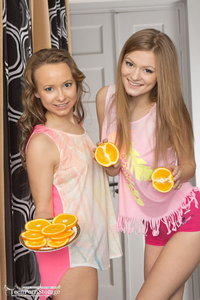 Young looking lesbians Alsu  Patritcy hold orange slices while getting naked