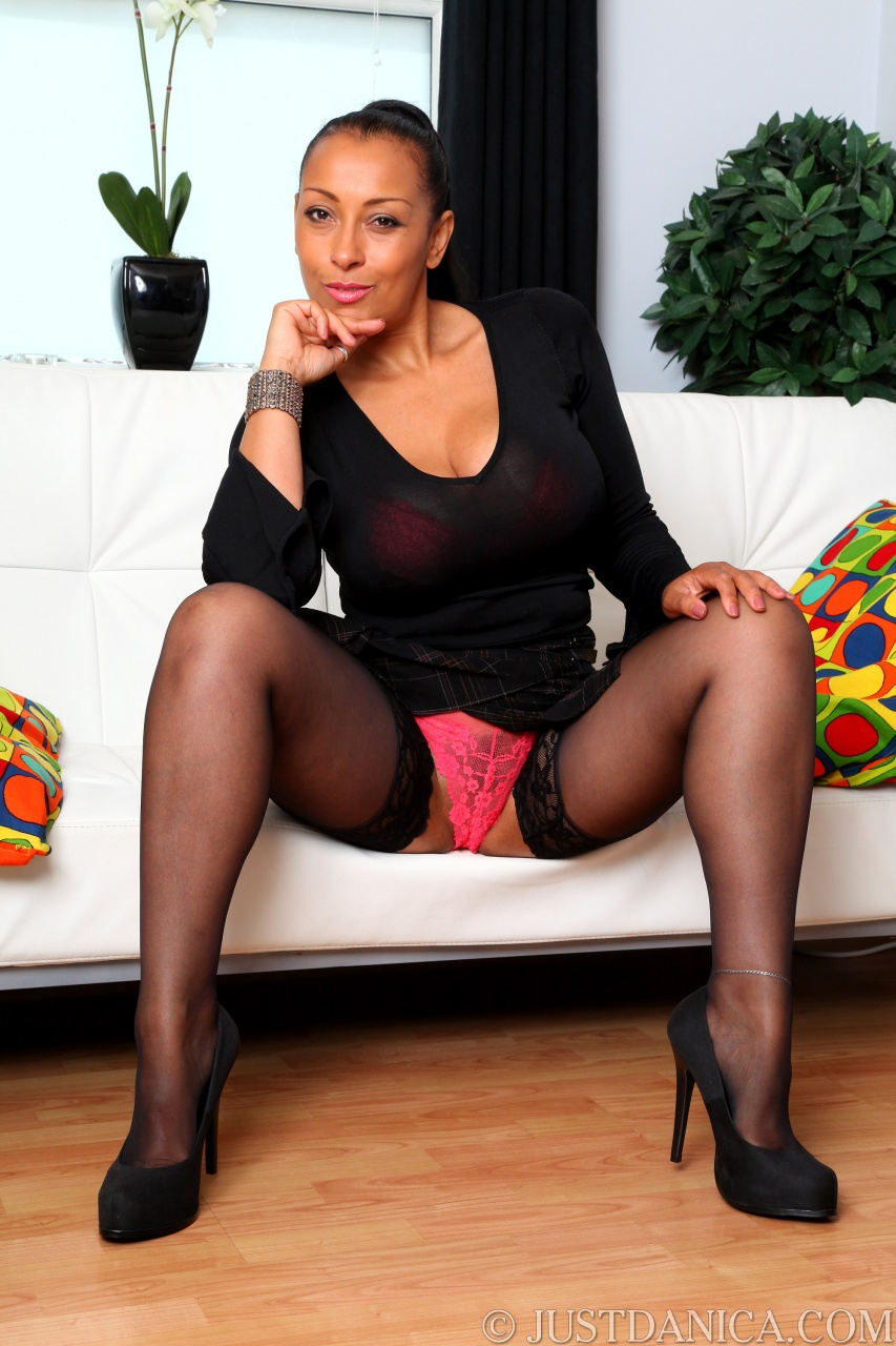Mature MILF Danica Collins draws attention to her bush while topless