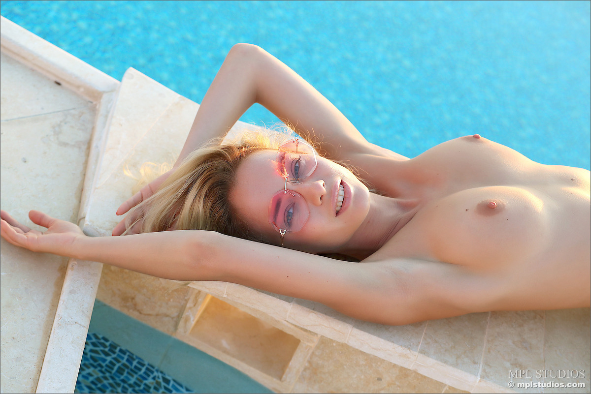 Blonde chick removes sunglasses and bikini to model naked in and out of a pool