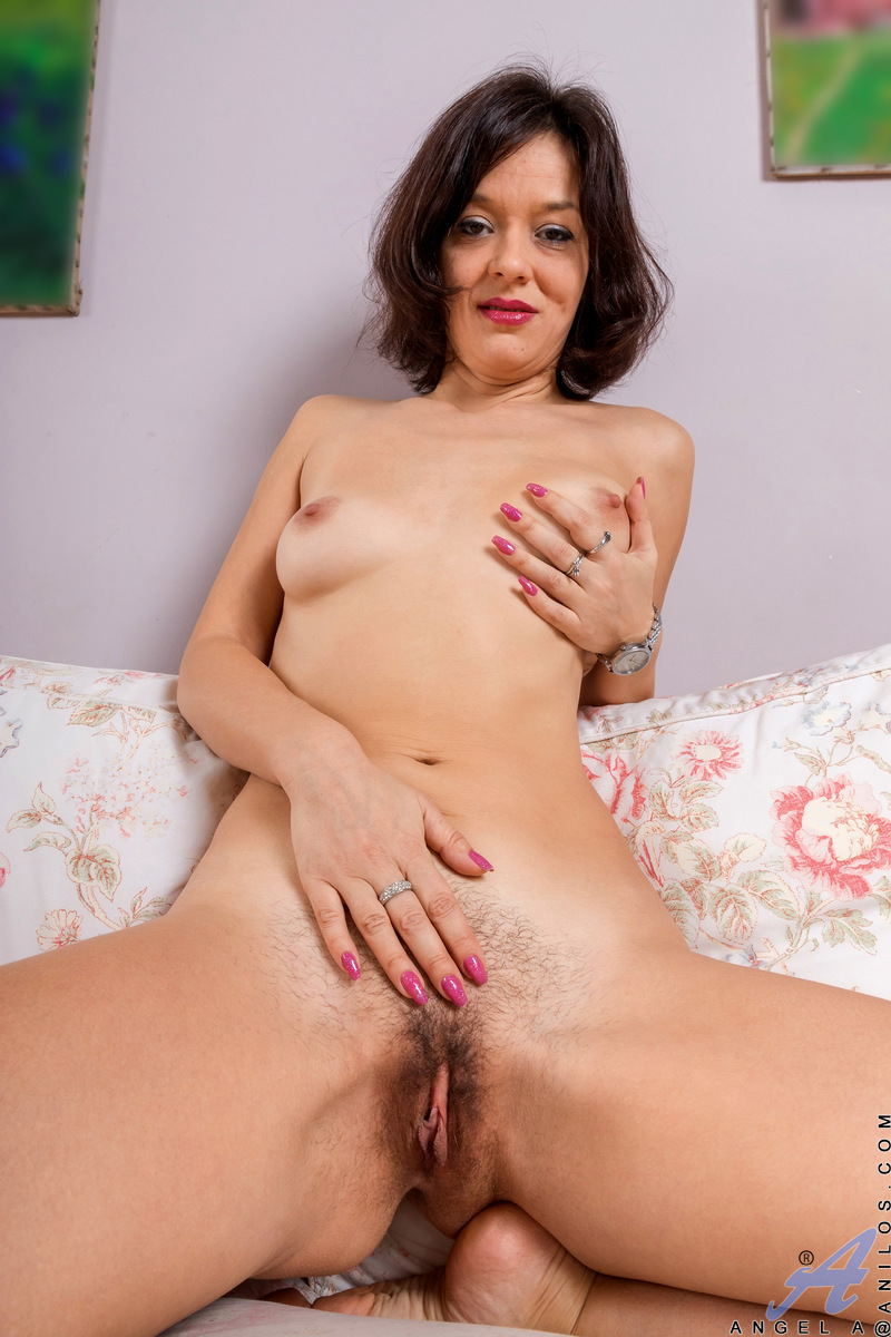 Sexy older lady Angel A pets her trimmed pussy after getting totally naked