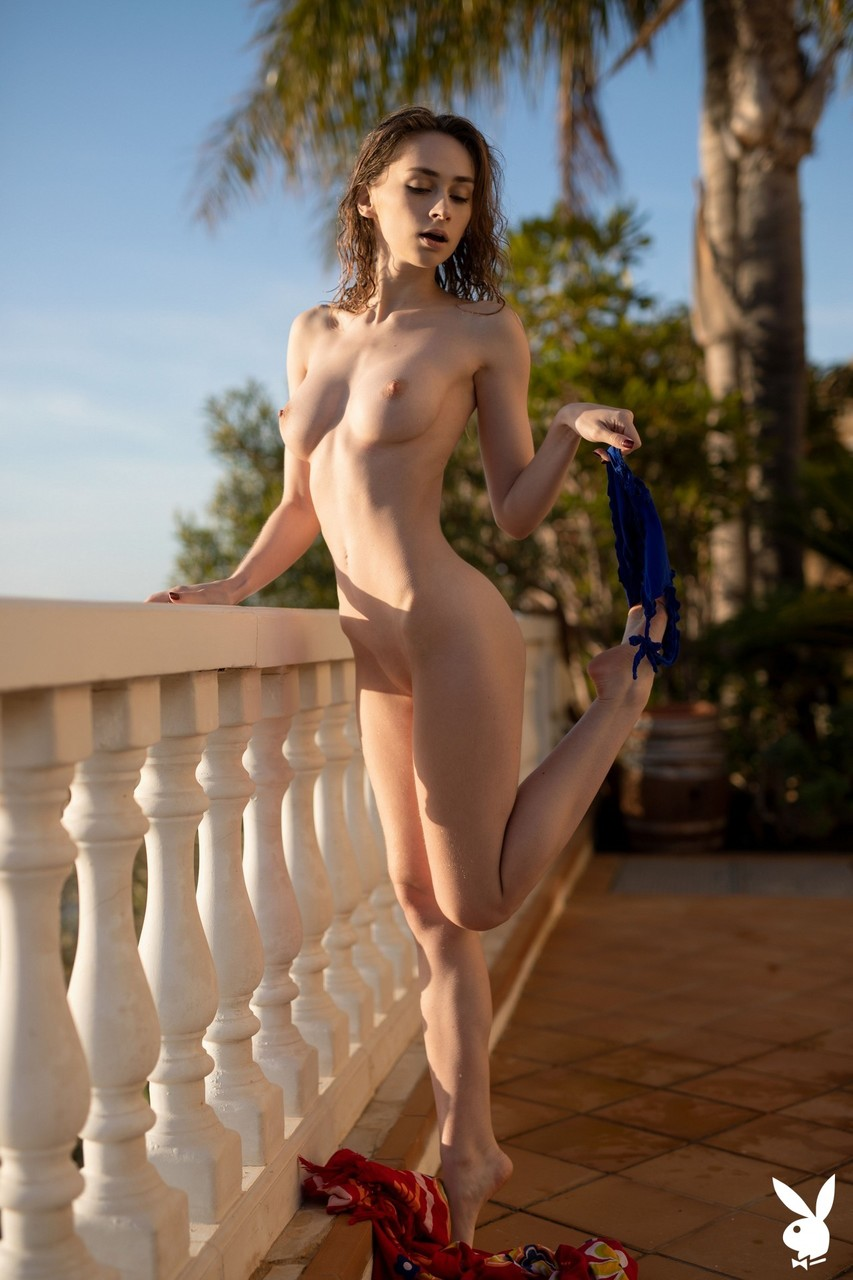 Centerfold model Yana West shows off her great body while naked by a baluster
