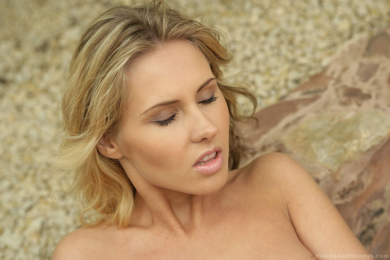 Blonde girl grabs her hot ass after getting naked outdoors in the courtyard