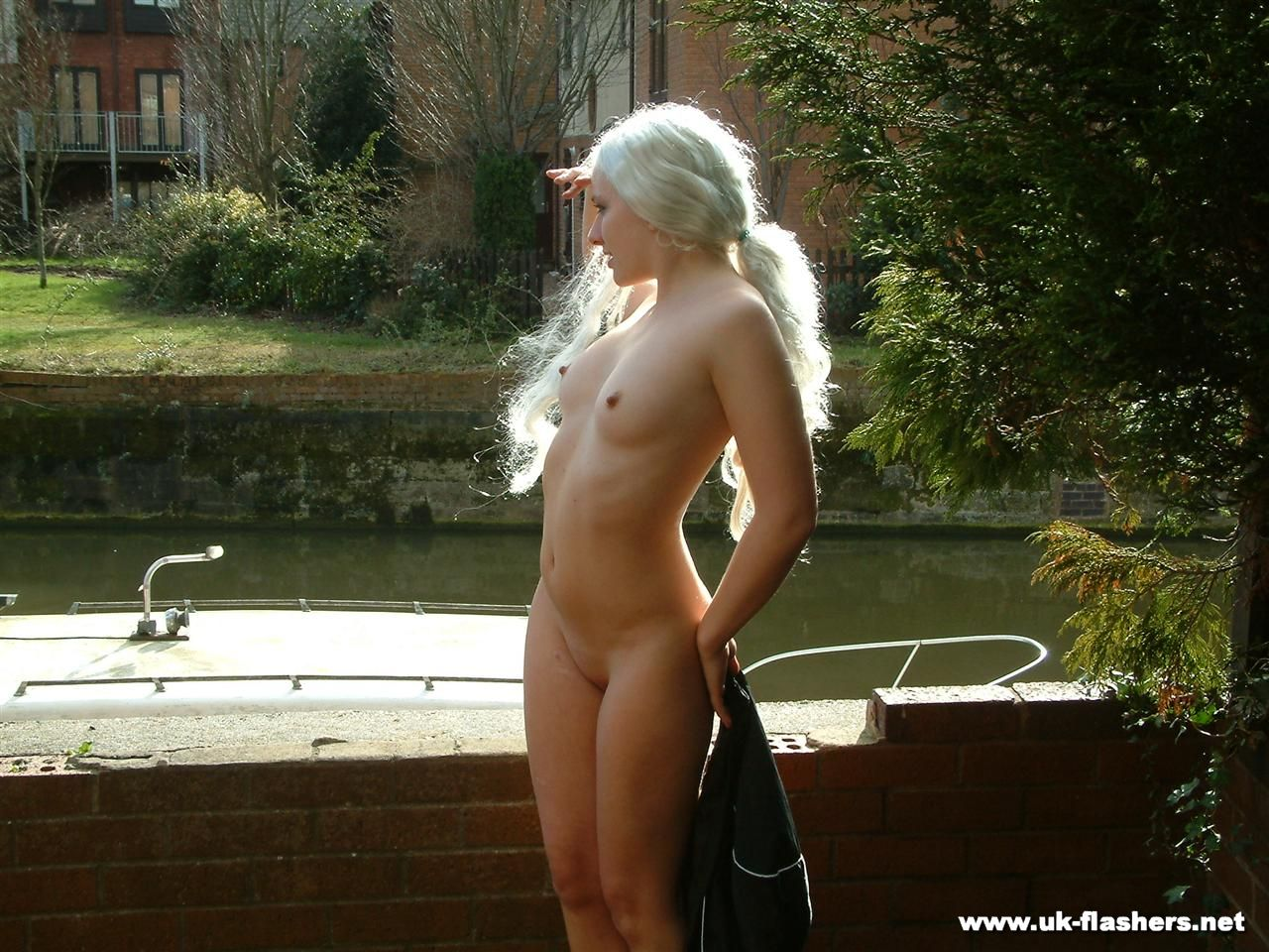 Platinum blonde chick gets completely naked on a boat dock before breast play