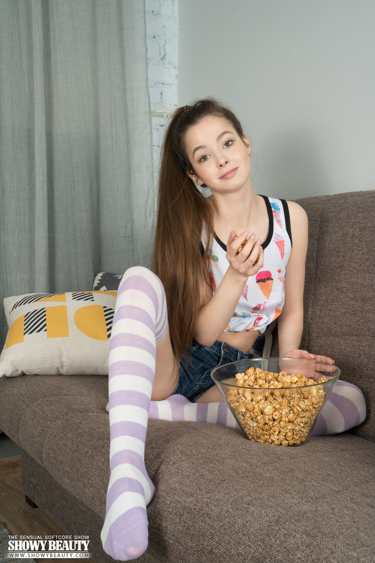 Young looking first timer Angela rolls off long socks to model totally naked
