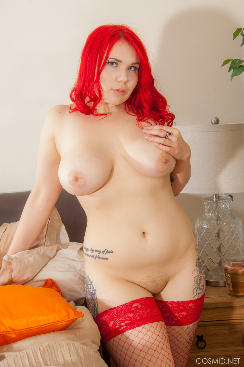 Thick redhead Red Ivy bares her natural tits as she disrobes to red fishnets