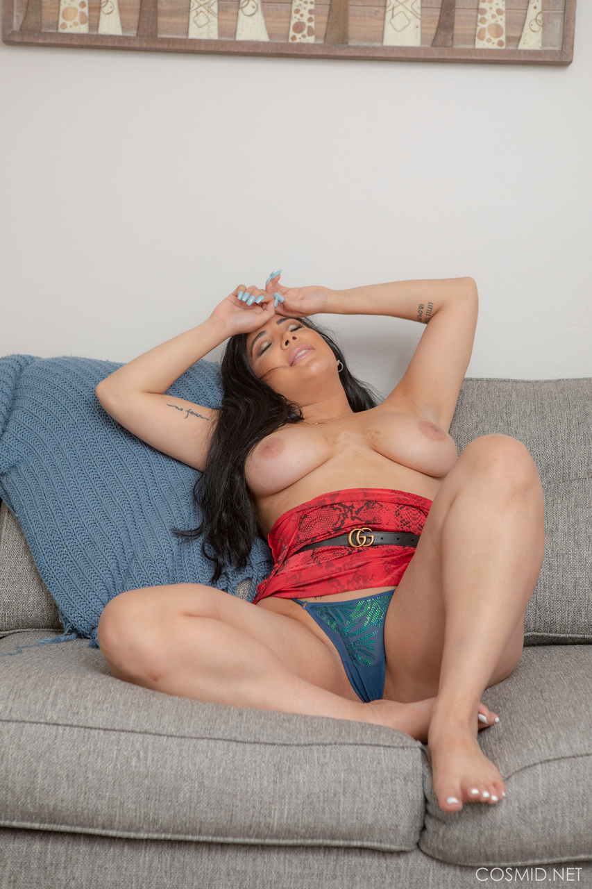 Thick Latina girl Juliana Cruz removes her red dress to model naked on a sofa