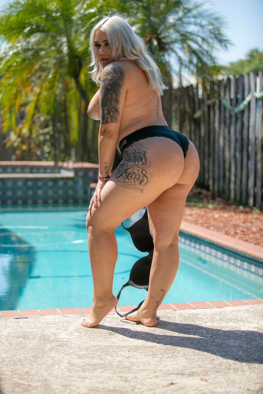 Tattooed BBW Blondie Franklin exposes her big butt while disrobing by a pool