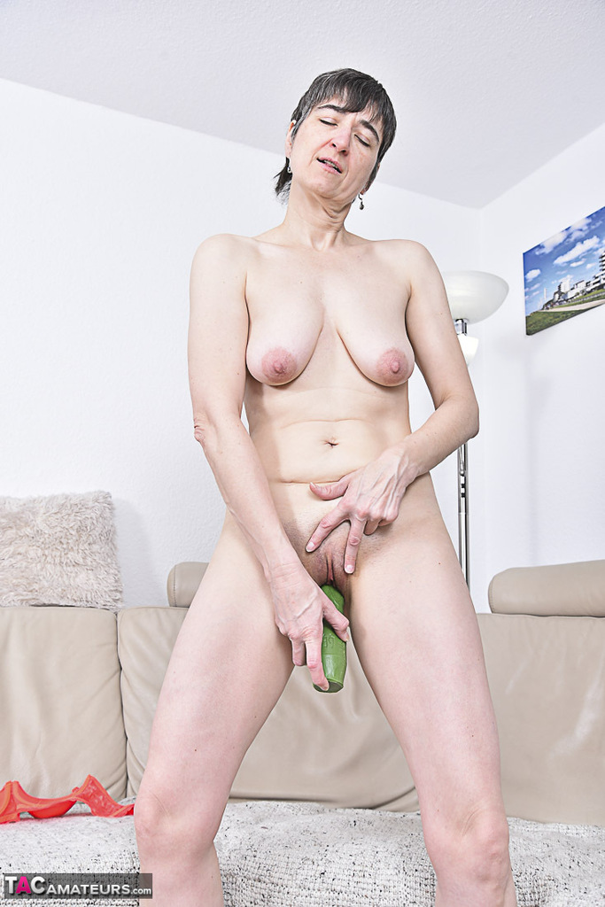 Short haired mature lady with saggy tits works a sex toy up her shaved pussy