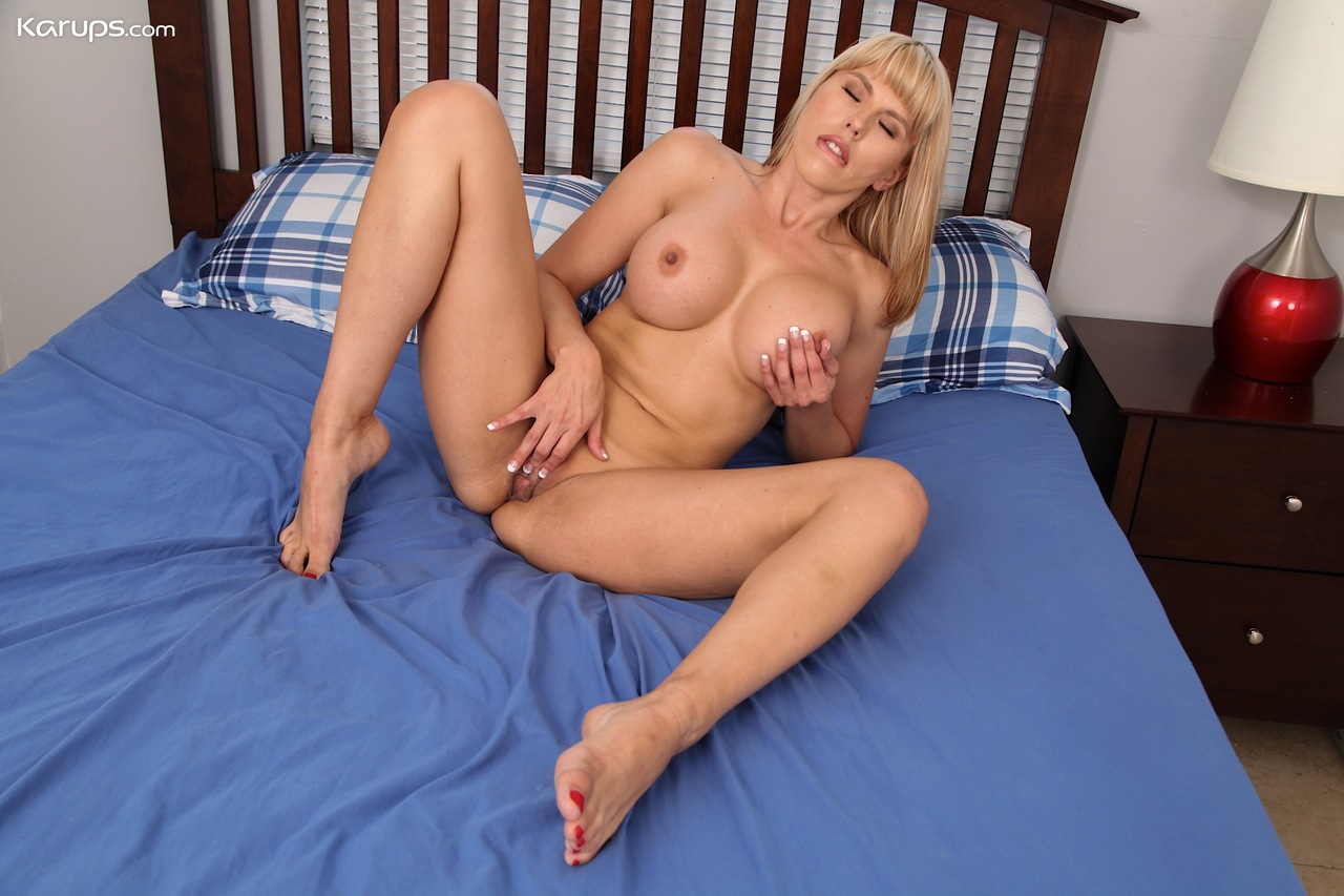 Blonde amateur Amber Chase uncups her enhanced tits as she undresses