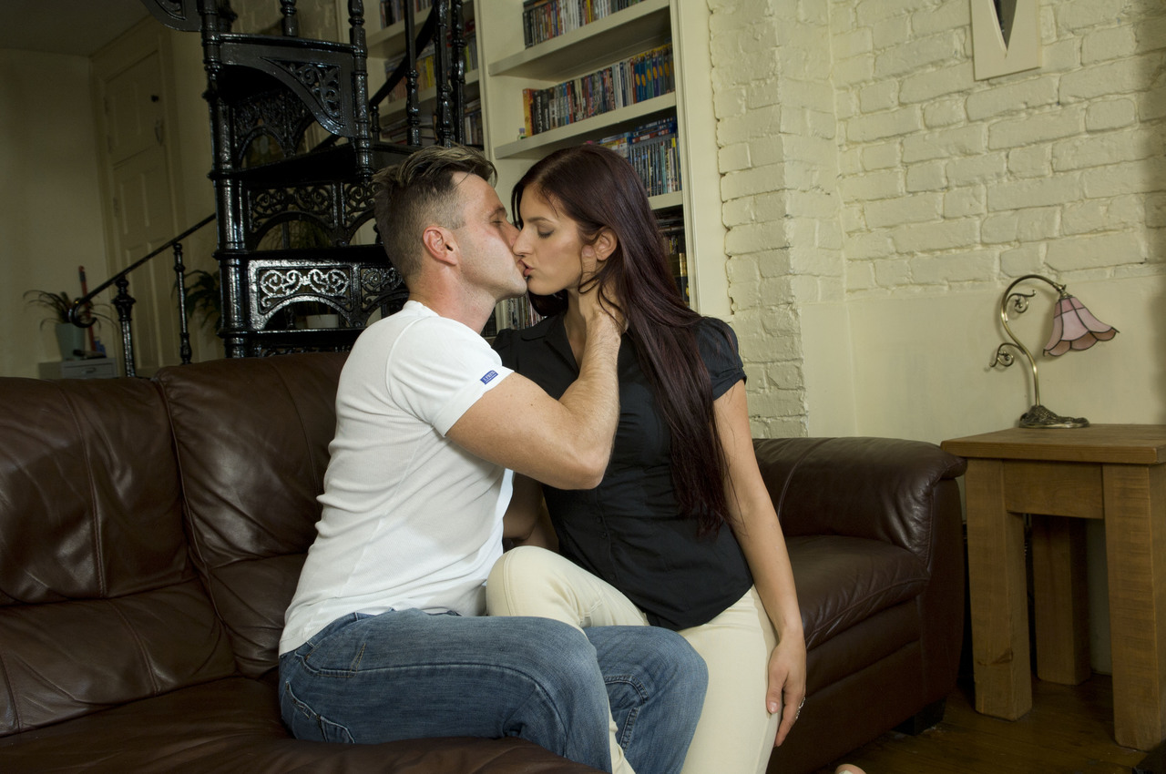Horny couple move onto intercourse on a leather couch after a quick kiss