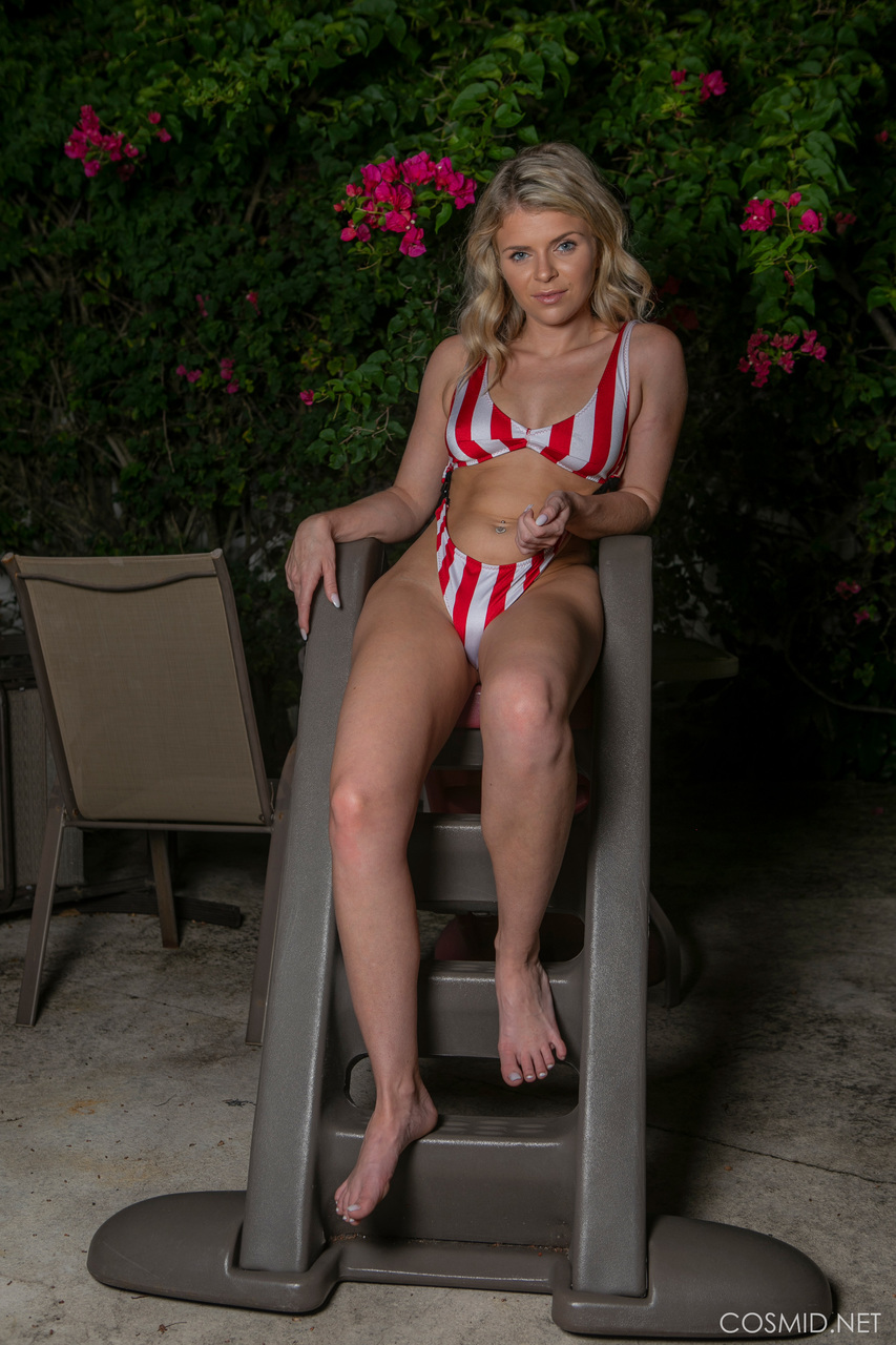 Natural blonde Kali Collins works clear of a one piece swimsuit on the patio