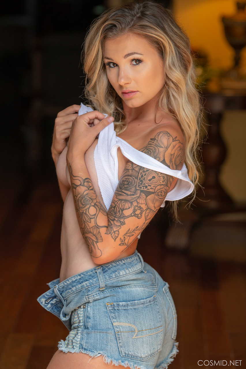 Tattooed blonde Julie Ambrose sheds a crop top and jean shorts to pose nude
