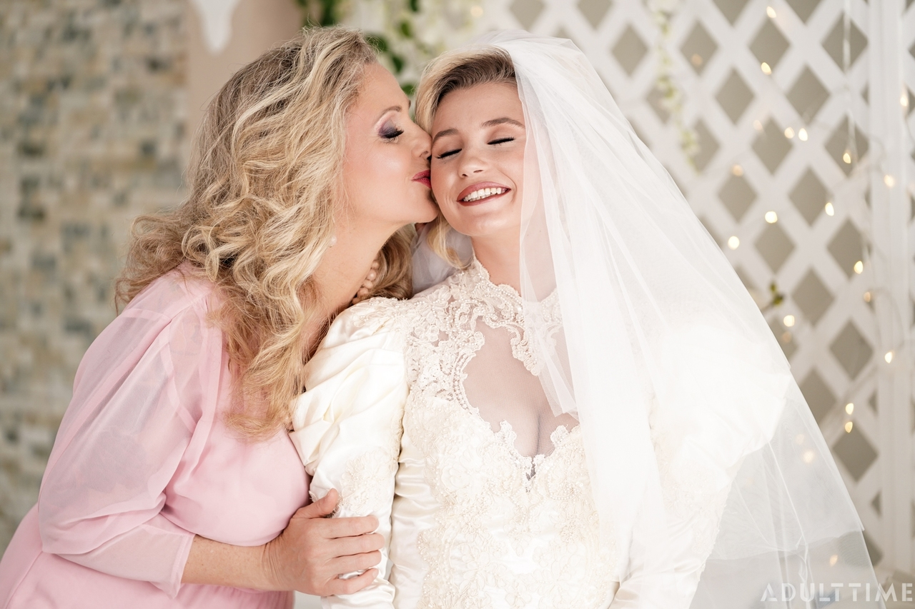Carolina Sweets is affixed with a garter before a lesbian wedding to Julia Ann