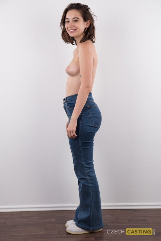 Amateur model Uliana stands naked after removing a sweater and blue jeans