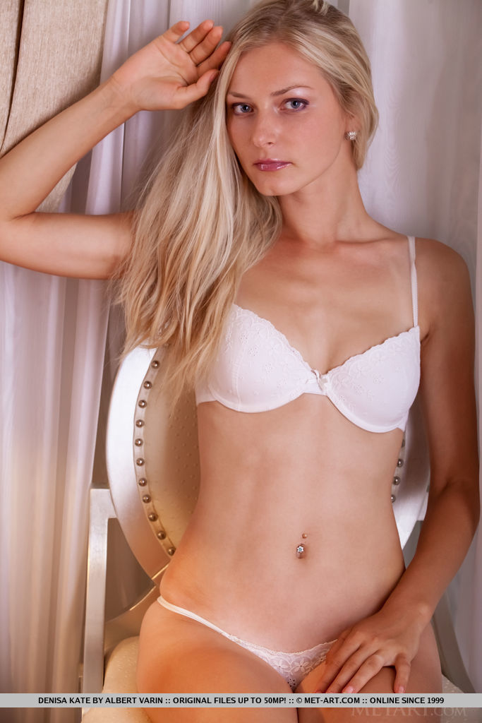 Natural blonde Denisa Kate slips off a bra and thong to pose nude afore drapes